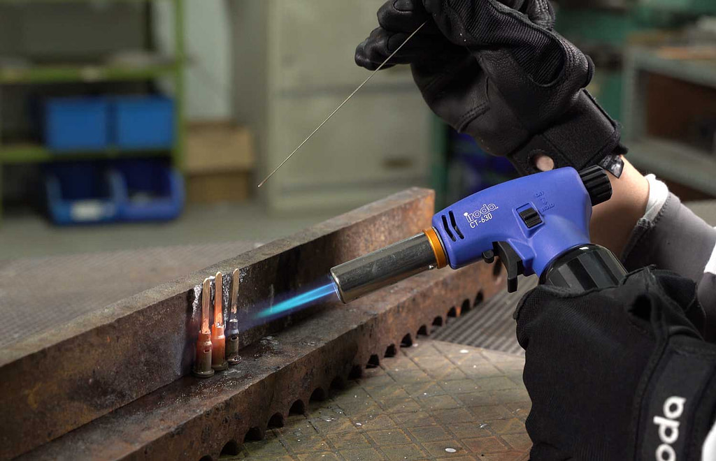 Pro-Iroda's CT-630 Professional Butane Torch with high output flame performing heavy duty welding in a factory
